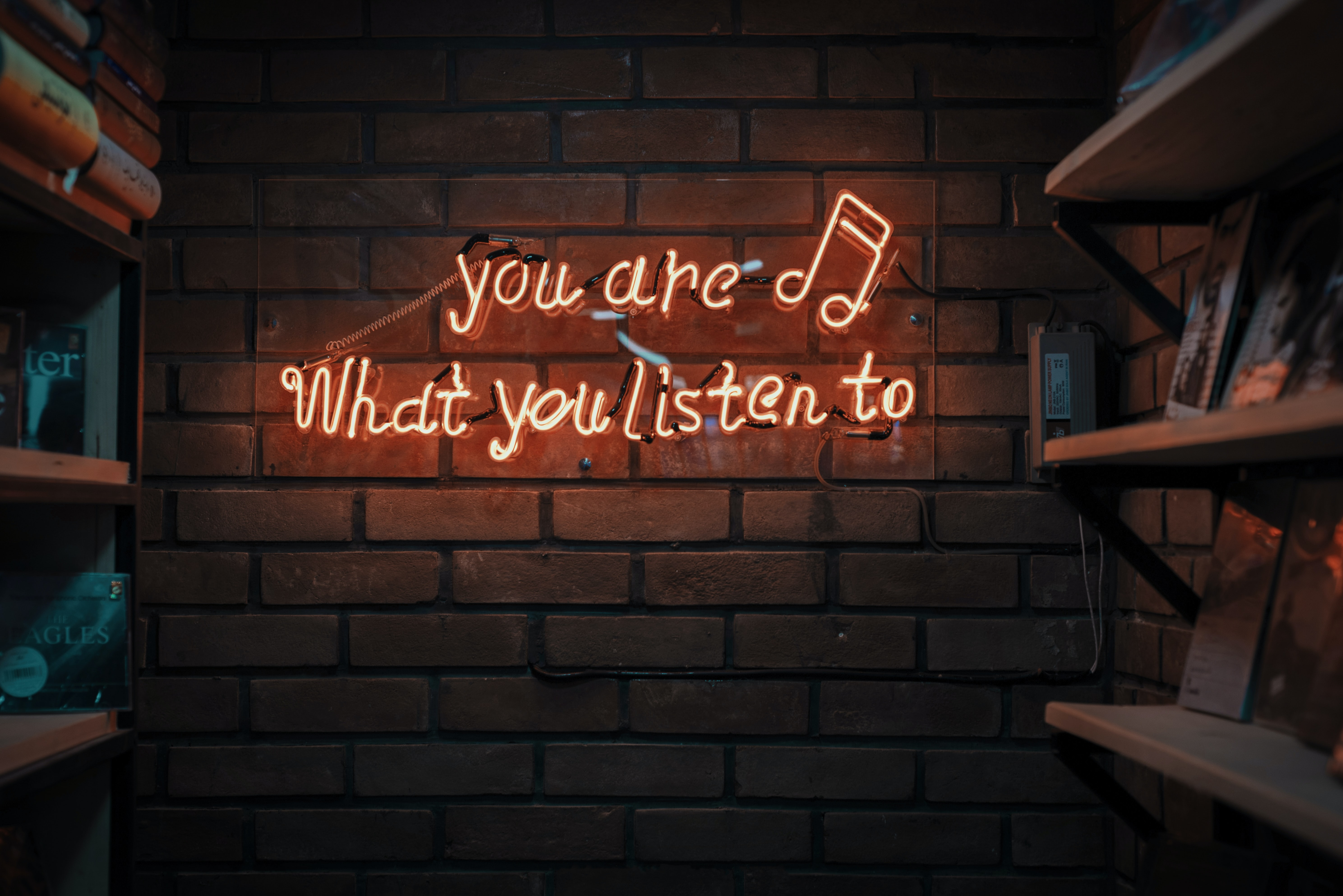 """fluorescent text on a brick wall that says """"you are what you listen to"""""""