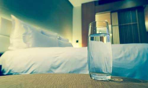 Why does the water by the bed taste different the next morning ?